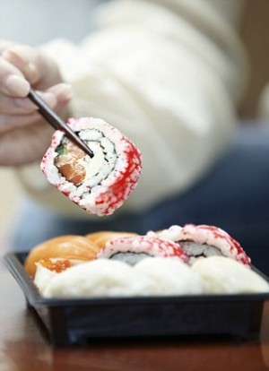 Hand holding chopsticks with sushi roll