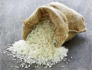 Raw long grain white rice grains in burlap bag